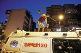 摆摊小贩爬上急救车顶 挥铁铲与城管对峙(图)