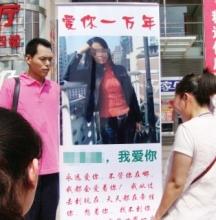 男子为挽回女友感情在街头举海报示爱