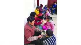 幼儿园没食堂 家长被阻入园寒风倚墙给孩子喂饭